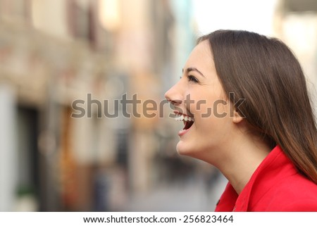 Profile of a woman face laughing happy in the street with an unfocused urban background - stock photo