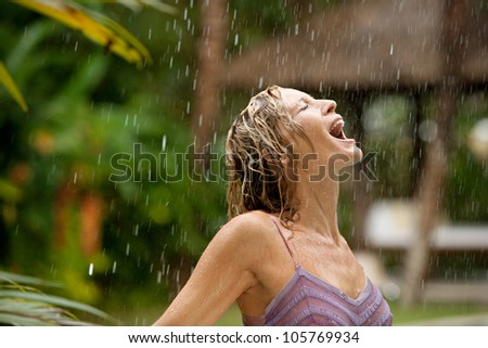 Profile of a young attractive woman under tropical rain with her mouth open. - stock photo