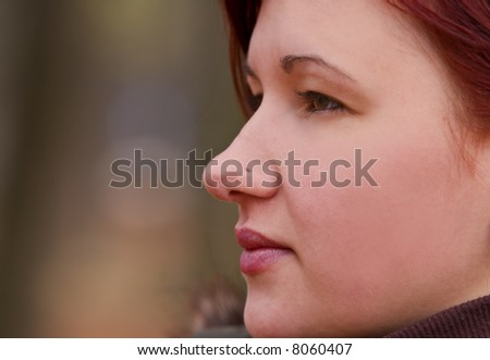 Profile of a young girl with a nose piercing. - stock photo