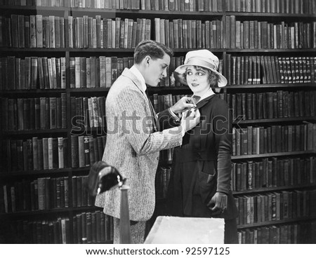 Profile of a young man attaching a brooch on a young woman's overcoat in a library - stock photo