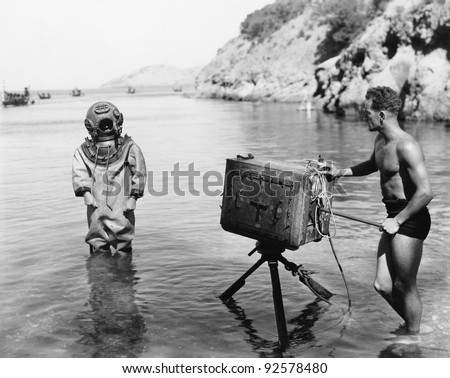 Profile of a young man holding a camera with a scuba diver standing in front of him on the beach - stock photo