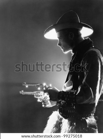 Profile of a young man holding guns - stock photo