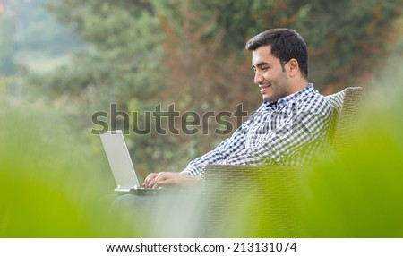 Profile of a young man with laptop, outdoor - outside. Side view sideways - stock photo