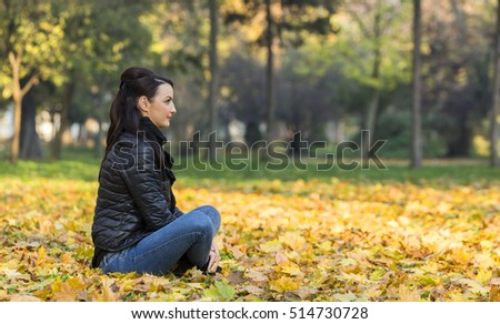 Profile of a young smiling woman in a yellow autumn forest.