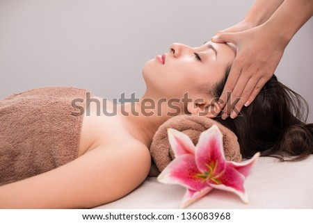 Profile of a young woman having head massage - stock photo