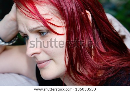 profile of a young woman in an anxious state, deep in thought looking worried - stock photo