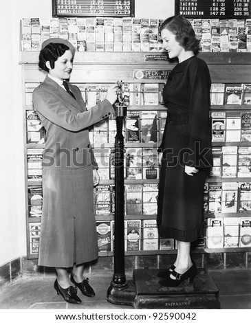 Profile of a young woman in an uniform measuring weight of another young woman on a weighing scale - stock photo