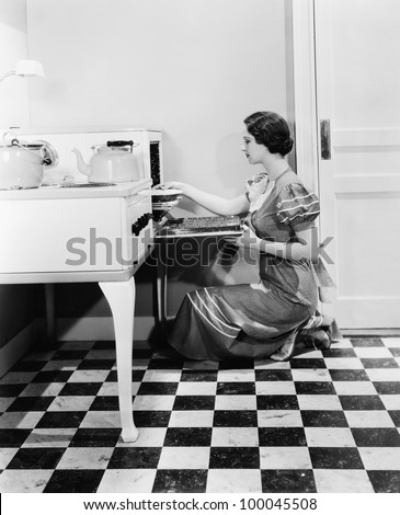 Profile of a young woman putting a pie into an oven - stock photo