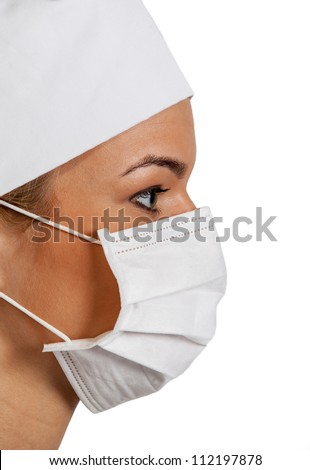 Profile of a young woman surgeon wearing a mask.