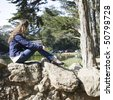 Profile of a Young Woman With Long Hair Sitting on Rocks in a Park - stock photo