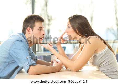 Profile of an amazed casual man looking at cleavage of annoyed girl who is saying him look me in the eyes during a date in a coffee shop - stock photo