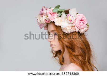 Profile of attractive young woman with wavy red hair in beautiful flower wreath over grey background - stock photo