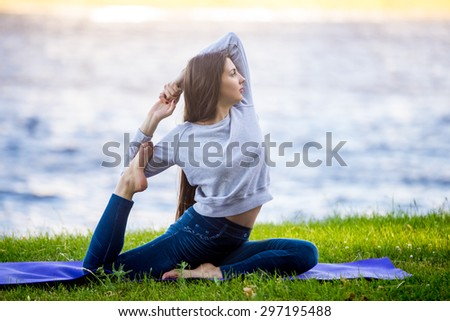 Profile of beautiful sporty young woman working out on city street, doing warming up stretching exercises on lake in park, sitting in Eka Pada Rajakapotasana, full length - stock photo