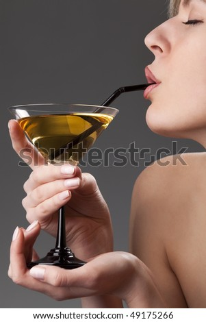 Profile of beautiful woman face with glass of cocktail - stock photo