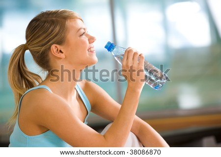Profile of beautiful woman going to drink some water from plastic bottle after workout - stock photo