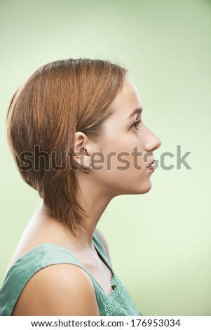 Profile of beautiful young woman, on green background. - stock photo