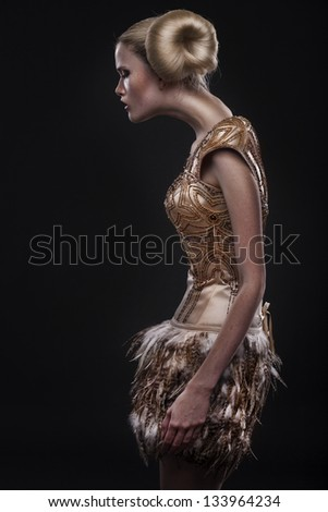 Profile of beautiful young woman with fashion hairstyle isolated on black background - stock photo