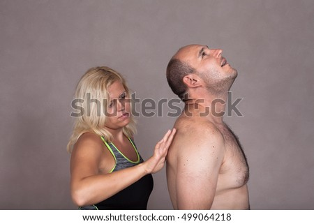 Profile of blonde woman giving a back massage to shirtless man.