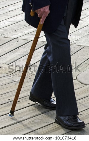 Profile of bottom half of an old man or elderly person walking with a wood cane stick wearing a dark suit. Concept photo of old age, health care, senior,  lifestyle, pensioner, retirement.   ,  - stock photo