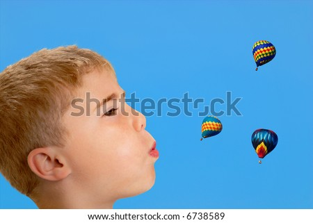 Profile of boy blowing at hot air balloons in sky