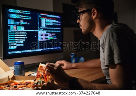 Profile of concentrated young software developer eating pizza and coding at home - stock photo