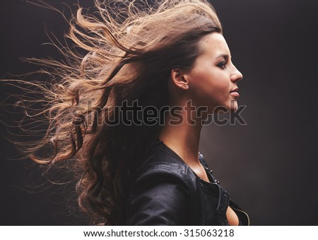 Profile of cool girl with long curly hair - stock photo