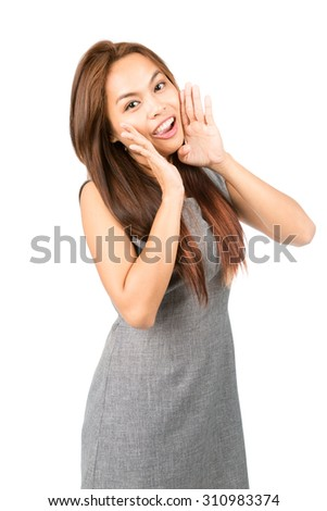 Profile of cute, happy Asian woman, sleeveless gray dress, light brown hair looking at camera, shouting announcement cupped hands around mouth. Thai national Chinese origin. Half length Vertical