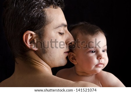 Profile of dad and baby. On dark background.