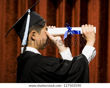 Profile of graduated boy with mortarboard looking through diploma - stock photo