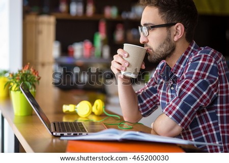 Profile of handsome freelance man drinking coffee while working on laptop computer in restaurant or cafe. Man in glasses thinking about business projects or strategies.