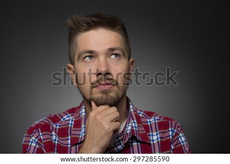 Profile of handsome man thinking and looking upwards. Man in maroon plaid shirt touching his beard and seriously looking somewhere. - stock photo
