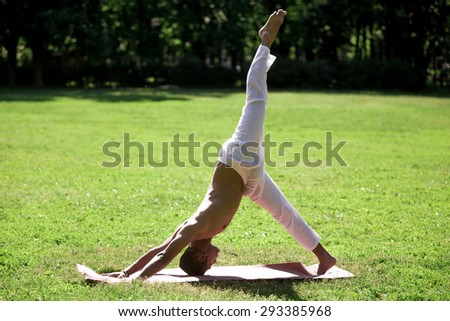 Profile of handsome sporty Indian young man exercising in park in summer, doing yoga, fitness or pilates training, standing in eka pada adho mukha svanasana, one-legged downward facing dog pose - stock photo