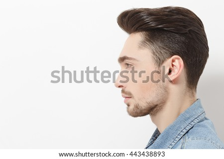 Profile of handsome young man in jeans shirt posing over white background. Male with modern hairstyle in studio. Hairdressing concept.