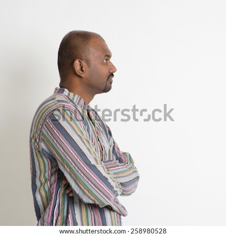 Profile of Indian male looking at blank copy space having a thought on plain background. - stock photo