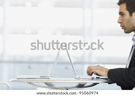 Profile of man typing on laptop - stock photo