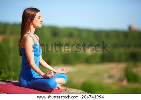 Profile of meditating woman relaxing in pose of lotus outdoors - stock photo