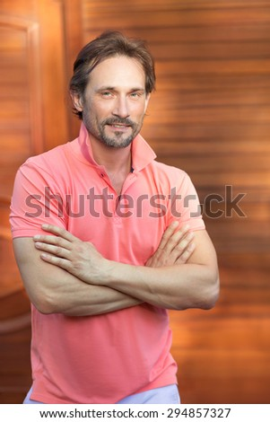 Profile of powerful rich man with his arms crossed. Man in coral T-shirt with beautiful hair-cut smiling isloted on brown.