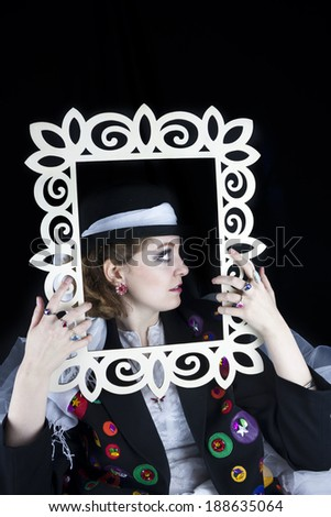 Profile of pretty young woman posing with picture frame wearing hat and crinoline.