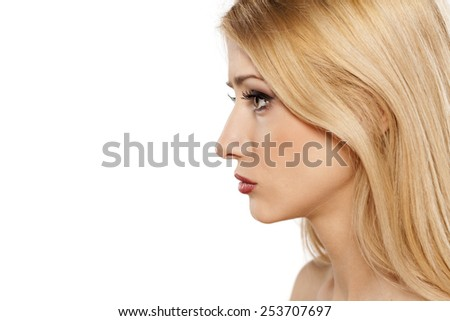 profile of sad young blonde on a white background