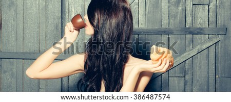 Profile of sensual attractive young woman with long brunette lush hair drinking coffee from cup holding big burger on wooden background, horizontal picture - stock photo