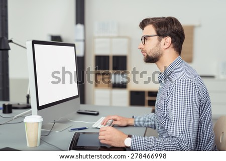Profile of Serious Young Businessman Wearing Eyeglasses and Checkered Shirt Working on Mac Computer at Desk in Office - stock photo