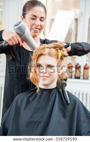 Profile of Smiling Young Woman with Long Red Hair Having Hair Cut and Styled by Stylist in Salon