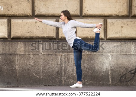 Profile of sporty young woman on street working out in front of building wall, standing in easy variation of Natarajasana, Lord of the Dance pose, full length