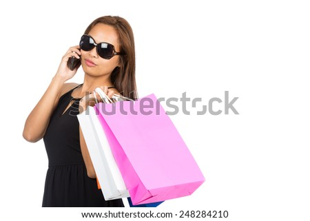Profile of stylish Asian woman shopping in modern fashion dress, sunglasses, drapes department store shopping bags over shoulder, talking on cell phone. Horizontal. Thai national of Chinese origin - stock photo