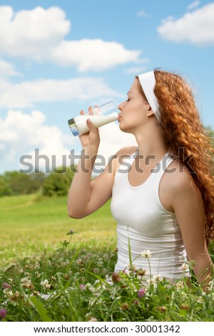 Profile of the beautiful girl drinking milk against a meadow and the blue sky - stock photo