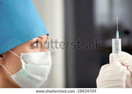 Profile of the doctor checking a syringe - stock photo