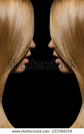 Profile of two women with straight hair on black background - stock photo