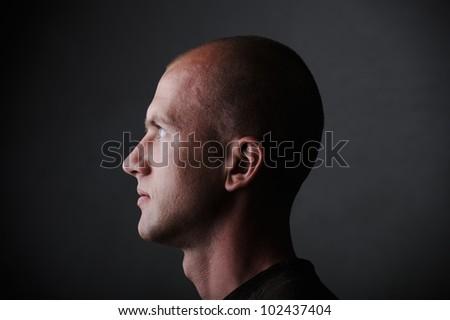 Profile of white bald man in his twenties in dark - stock photo