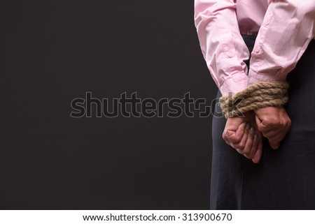 Profile of woman's tied up hands with strong rope. Lady in pink shirt keeping hands behing her back. She is thinking about way out.