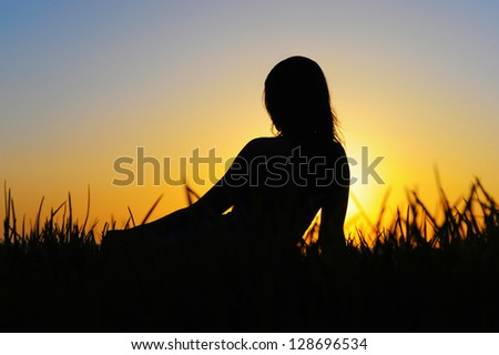 Profile of woman sitting on the grass near the sea at sunset